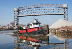 Tugboat and Drawbridge. After clearing a raised drawbridge a small harbor tugboat makes its way toward the open waters of Lake Erie from the Cuyahoga River in stock images