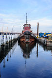 Tugboat and Dredge Barge. Tugboat and barge docked for the night. Vessel's weathered and rusted hull is reflected in blue harbor water in foreground. Blue sky Stock Photography