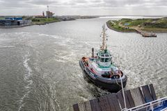 Tugboat in Dutch harbor IJmuiden supporting ferry to English Newcastle royalty free stock photography