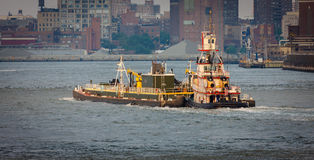 Tugboat on East River, New York. East River, NYC: a tugboat is pushing a barge upstream. View of Brooklyn in the background Stock Photo