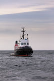 Tugboat floating in wait on calm ocean at anchor Stock Images