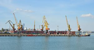 Tugboat and freight train under port crane Royalty Free Stock Images