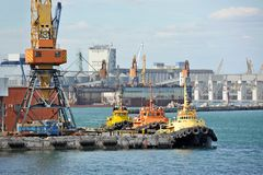 Tugboat and freight train under port crane Royalty Free Stock Photography