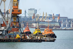 Tugboat and freight train under port crane Stock Images