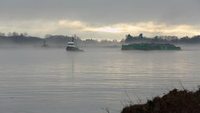 Tugboat and Gravel Barge, Fraser River Mist. A tugboat tows a gravel barge up the Fraser River through the early morning mist. Vancouver, British Columbia stock footage
