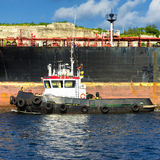 Tugboat guiding a huge cargo ship Stock Photos