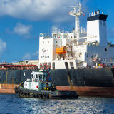 Tugboat guiding a huge cargo ship Stock Images