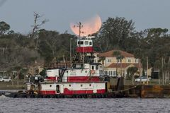 Tugboat under supermoon eclipse. A tugboat on the Halifax River in Ormond Beach, FL sails under the setting supermoon as a lunar eclipse takes place, January Stock Photography