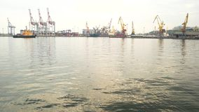 Tugboat and harbor cranes. Port at daytime. Marine industry jobs stock footage