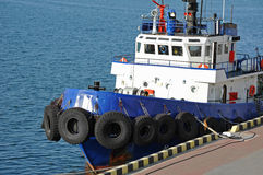 Tugboat in harbor quayside Stock Images
