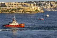 A tugboat at Kalkara Creek, Grand Harbor, Port of Valletta, Malta. A tugboat in front of the Bighi Complex behind a container ship leaving Grand Harbor Malta Royalty Free Stock Photography