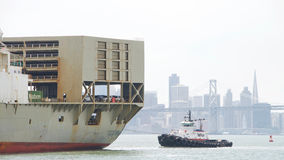 Tugboat LIBERTY assisting Cargo Ship MATSONIA to maneuver Stock Images