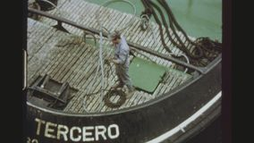 Tugboat Maneuvers In Port. SPAIN, GRAN CANARIA, LAS PALMAS, NOVEMBER 1972. Four Shot Sequence Of A Tugboat Towing A Cargo Ship Into The Port. Male Worker Working stock video