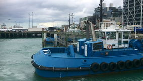 Tugboat mooring at Captain Cook Wharf in Ports of Auckland, New Zealand. Tugboat, small, strongly built vessel, used to guide large oceangoing ships into and stock footage