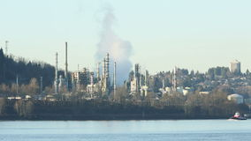 Tugboat and Oil Refinery, Burrard Inlet. A tugboat crosses in front of an oil refinery on the shore of Burrard Inlet, British Columbia, Canada near Vancouver stock video