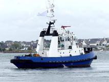 Tugboat in operations. Blue and white Tug Boat in operations  at Lorient harbor, France. Horizontal  three-quarter stern view Royalty Free Stock Photography