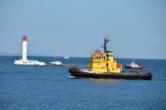 Tugboat over lighthouse Stock Photos