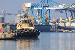 Tugboat is at the pier in the sea port. Cargo port royalty free stock image