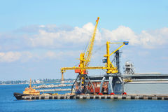 Tugboat and port cargo crane Royalty Free Stock Images