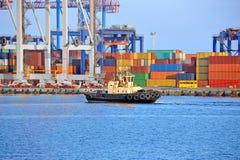 Tugboat and port cargo crane Stock Photos