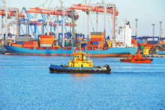 Tugboat and port cargo crane Stock Images