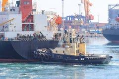 Tugboat przy łękiem ładunku statek, pomaga naczynie manewrować w porcie morskim zdjęcia royalty free
