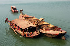Tugboat pulling  barge of sand. In river Stock Photography