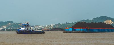 Tugboat pull heavy loaded barge of coal royalty free stock photo