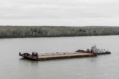 Tugboat pushes barge up the river royalty free stock photography