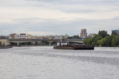 Tugboat pushing a heavy barge on the river Stock Photos