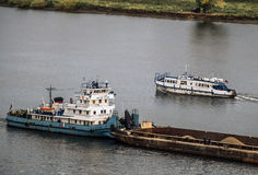 The tugboat pushing a loaded barge on the river. Towboat, pushing the loaded barge on the river. I met a river bus Royalty Free Stock Images