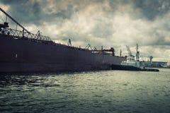 Tugboat pushing a ship Stock Photos