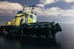 Tugboat ran aground, starry night sky with clouds. Long exposure stock photography