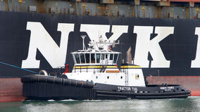 Tugboat ROBERT FRANCO off the port side of NYK APHRODITE Royalty Free Stock Photo