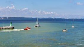 Tugboat and sailboats Stock Image