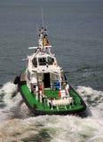 Tugboat sailing in the sea. Tugboat making maneuvers. Tugboat sailing through waves Royalty Free Stock Image