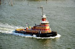 Tugboat sailing to assist with berthing of cargo vessel, New York Bay royalty free stock photography