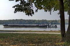 Tugboat with ship pass along the riverside park in Ruse town Stock Photo