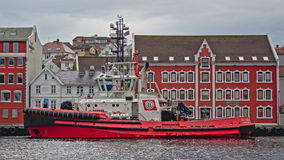 Tugboat in Stavanger harbour. Boa Odin tug boat moored in Stavanger inner city harbour in front of traditional red and white house Stock Photography