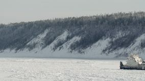 Tugboat stucked on river covered with ice in winter at background of snow forest stock video