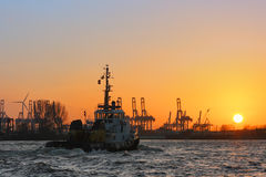 Tugboat at sunset on the Elbe river. Royalty Free Stock Image