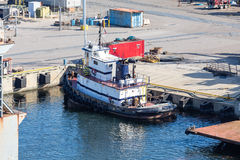 Tugboat Tied to Industrial Pier Stock Photo