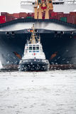 Tugboat towing freighter in harbor Royalty Free Stock Images