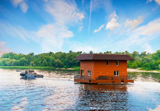 Tugboat towing house by river, Dnieper, Kiev, Ukraine Royalty Free Stock Image