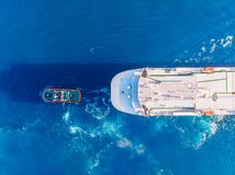 Tugboat Towing Large Container Ship Blue Sea Port. Aerial Top View Stock Image