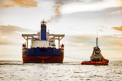 Tugboat towing a ship Stock Photo
