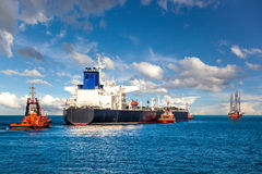 Tugboat towing a tanker. Oil Platform and Tanker in the Sea royalty free stock photo