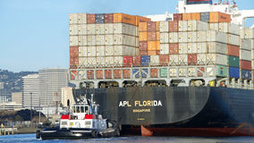 Tugboat VETERAN assisting APL FLORIDA to maneuver Royalty Free Stock Photos
