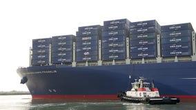 Tugboat VETERAN assisting CMA CMG BENJAMIN FRANKLIN to maneuver Royalty Free Stock Image