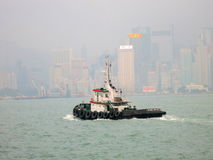 A Tugboat in Victoria Harbour Hong Kong in Front of Skyline Stock Photography